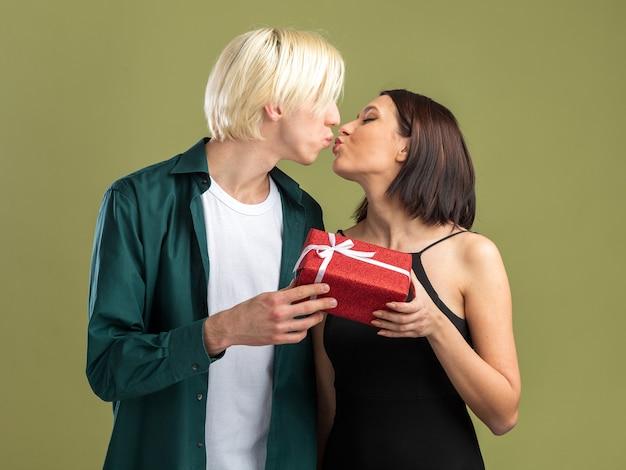 Amorosa pareja joven en el día de san valentín, ambos con paquete de regalo besándose aislado en la pared verde oliva