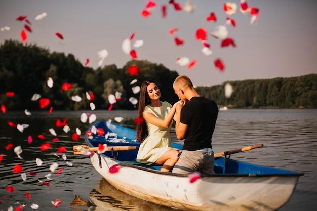 Amorosa pareja joven disfrutando de un barco en el lago