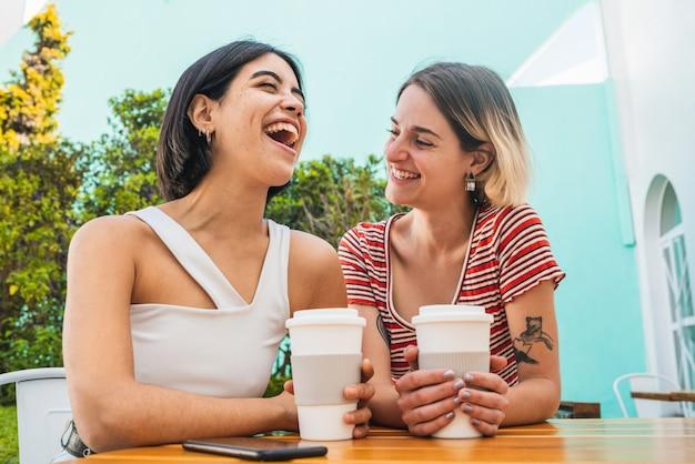 Amorosa pareja de lesbianas tener una cita en la cafetería.