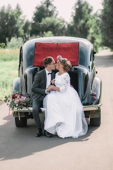 Amorosa pareja marido y mujer están sentados en el maletero de un coche retro besándose el día de su boda.