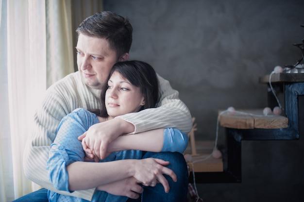 Amorosa pareja sentada abrazando en la escalera decorada con guirnaldas de navidad