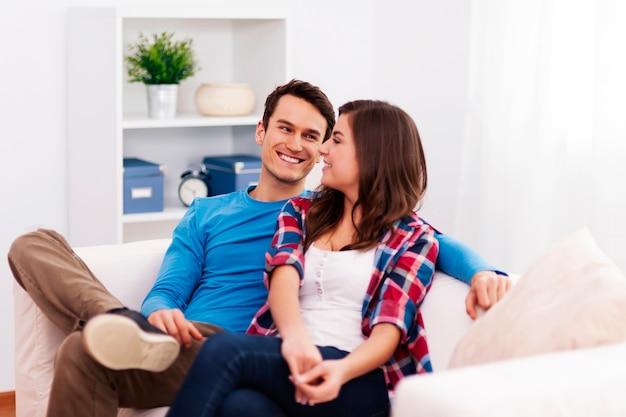 Amorosa pareja sentada en la sala de estar