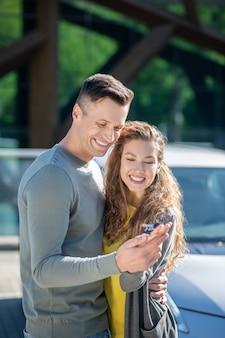 Amoroso hombre y mujer de pie abrazando mirando la llave