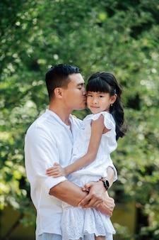 Amoroso padre asiático sosteniendo a su hija en sus manos, besándola en la mejilla. ella está mirando a la cámara. están pasando tiempo en un parque, disfrutando de los últimos días cálidos de principios del otoño.