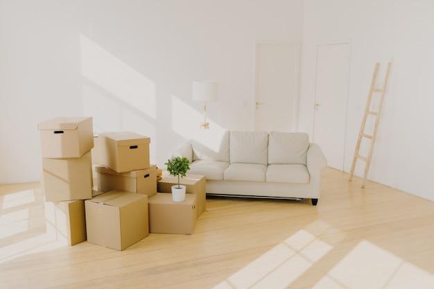 Amplia habitación con sofá, montones de cajas de cartón y escalera.