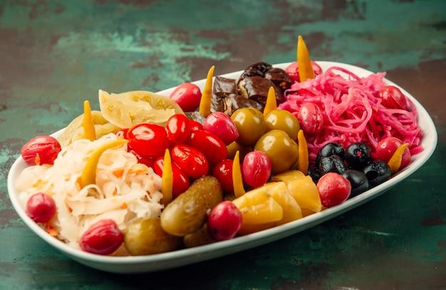 Amplia selección de frutas y verduras marinadas en un plato blanco.