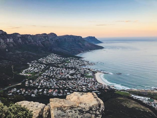 Amplia toma aérea de casas en la orilla del mar rodeado de montañas bajo un cielo azul y rosa
