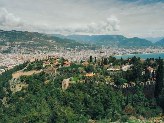 Amplia vista a la ciudad de alanya con ruinas del castillo en la vista frontal.