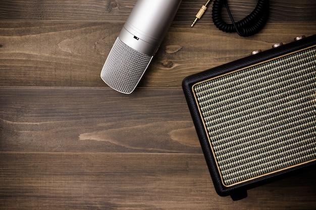 Amplificador de guitarra y micrófono sobre fondo de madera. estilo efecto vintage.