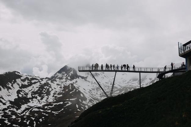 Amplio ángulo de disparo bajo de personas en un muelle cerca de montañas cubiertas de nieve