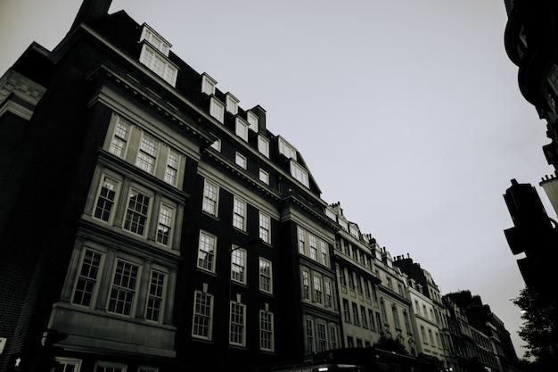 Amplio ángulo bajo en escala de grises de edificios con ventanas una al lado de la otra
