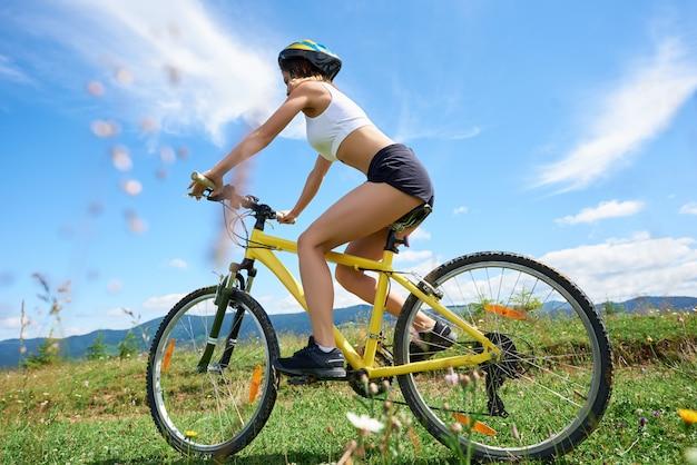 Amplio ángulo de visión de atleta femenina ciclista montando en bicicleta de montaña amarilla en un sendero rural, contra el cielo azul con nubes. actividad deportiva al aire libre