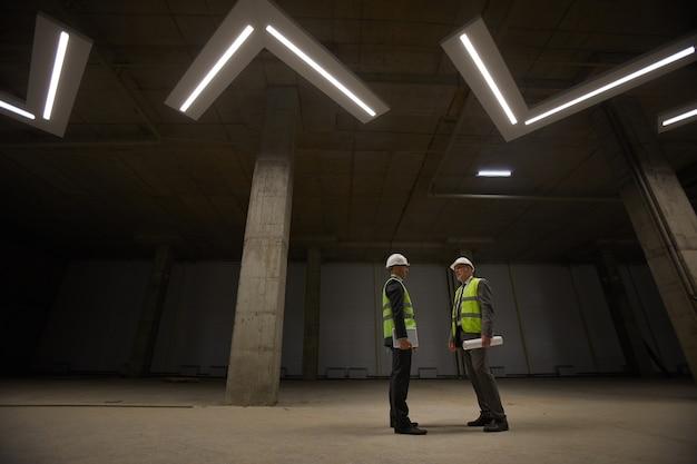 Amplio ángulo de visión en dos empresarios con cascos discutiendo el acuerdo de inversión mientras está de pie en el sitio de construcción,