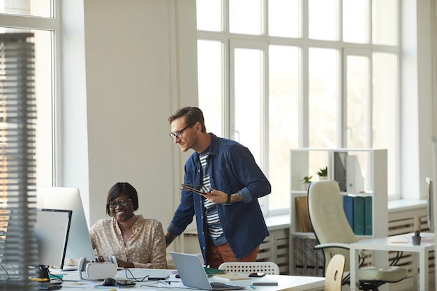 Amplio ángulo de visión en el gerente masculino que supervisa al empleado que trabaja con la computadora en la oficina blanca moderna, espacio de copia