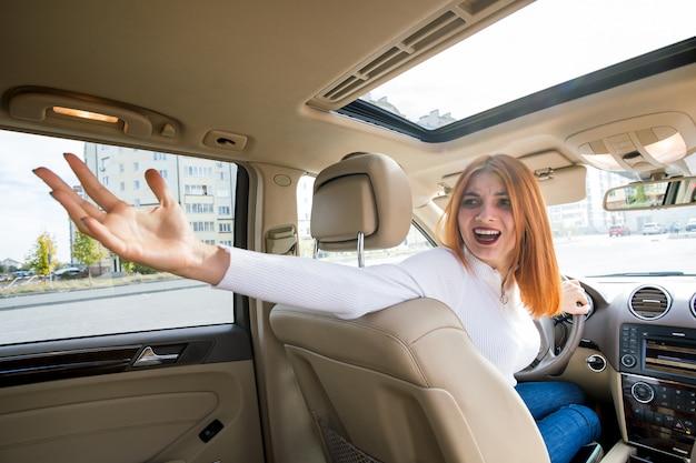 Amplio ángulo de visión de la joven pelirroja mujer conductora conduciendo un coche hacia atrás mirando hacia atrás.