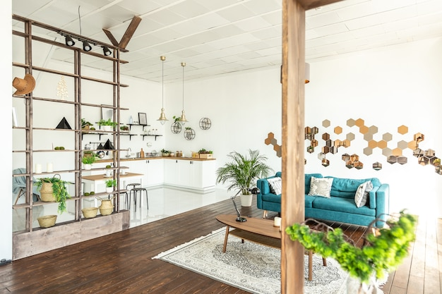 Amplio apartamento tipo estudio decorado con madera y blanco. diseño minimalista con enormes ventanales a la luz del sol. área de cocina y sala de estar