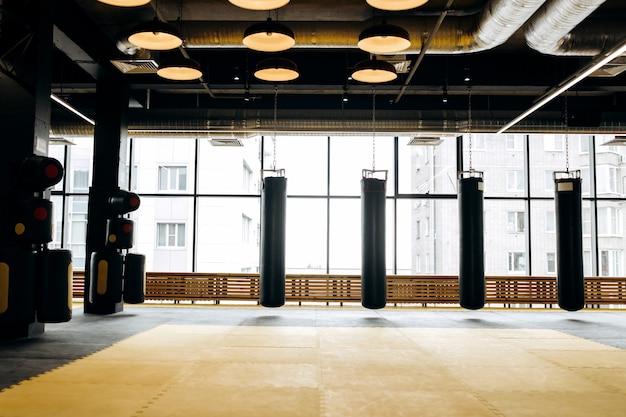 Amplio gimnasio con ventanales panorámicos y tres sacos de boxeo.