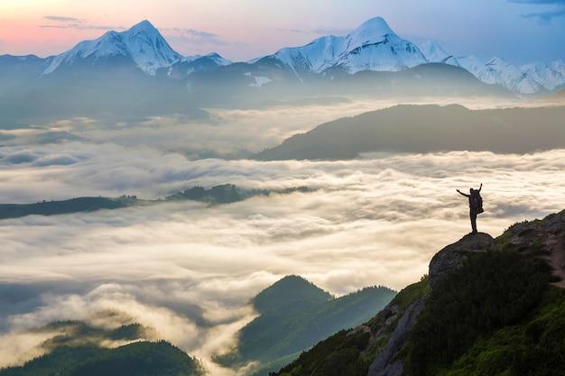 Amplio panorama de montaña. pequeña silueta de turista con mochila en la ladera de la montaña rocosa con las manos levantadas sobre el valle cubierto de nubes blancas y esponjosas. belleza de la naturaleza, turismo y concepto de viaje.