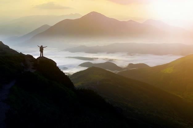Amplio panorama de montaña. pequeña silueta de turista con mochila en la ladera de la montaña rocosa con las manos levantadas sobre el valle cubierto de nubes blancas y esponjosas.