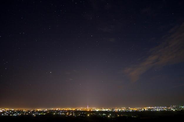 Amplio panorama, vista aérea nocturna de la ciudad turística moderna de ivano-frankivsk, ucrania. escena de luces brillantes de edificios altos, alta torre de televisión y suburbios verdes sobre fondo de cielo de estrellas de la noche.