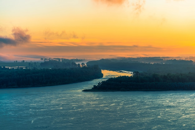 Amplio río azul fluye a lo largo de la costa con bosque bajo la niebla.