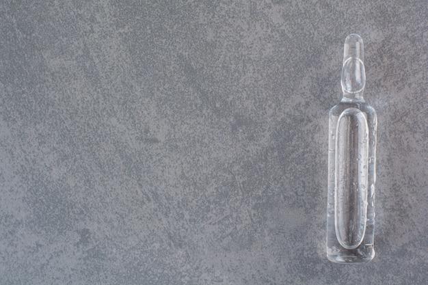 Ampolla médica transparente sobre mesa de mármol.
