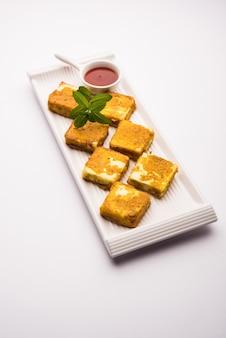 Amritsari paneer tikka hecho con cubos de requesón bañados en una masa hecha con besan, chat masala y especias y frito poco profundo en una sartén, servido con salsa de tomate