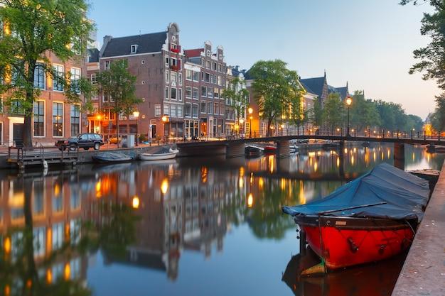 Amsterdam canal kloveniersburgwal con casas típicas holandesas, puentes y casas flotantes durante la hora azul de la mañana, holanda, países bajos.