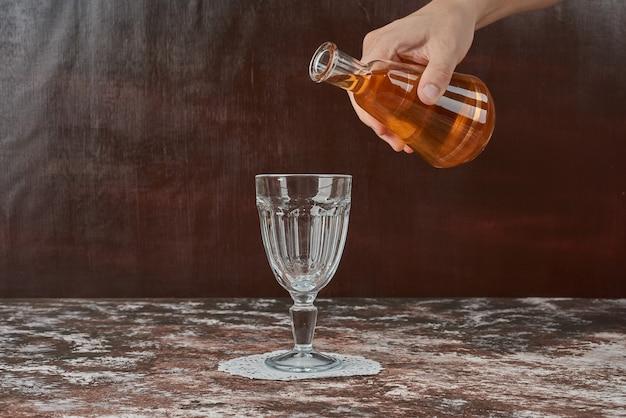 Añadiendo bebida en un vaso vacío.