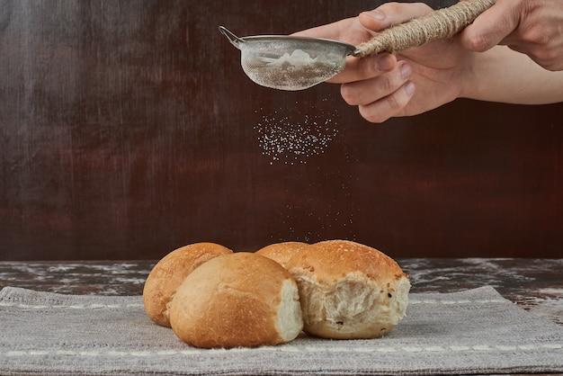 Añadiendo polvo blanco al bollo de pan.