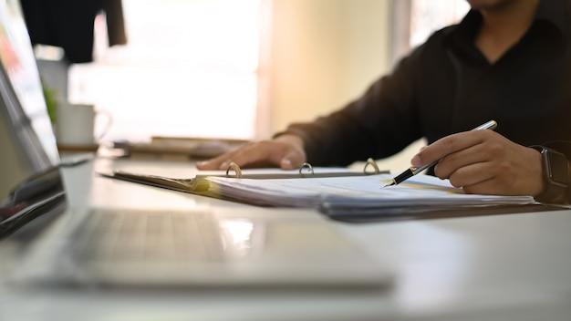 Análisis del hombre de negocios en el papel del documento con el tiro cosechado.