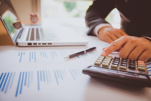Análisis de negocios - calculadora, hoja, gráficos y analista de la mano