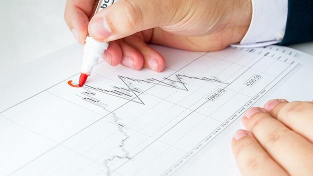 Analista financiero masculino escribiendo gráfico o gráfico financiero.