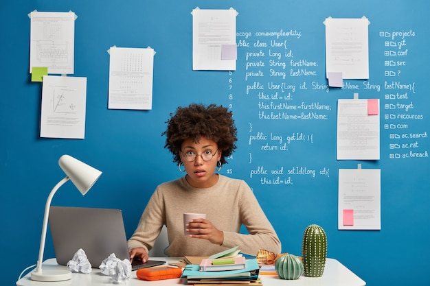 Analista informático sorprendido desconcertado tiene un descanso para tomar café, lee publicado en la página web, usa gafas redondas, posa en el escritorio contra la pared azul con información escrita