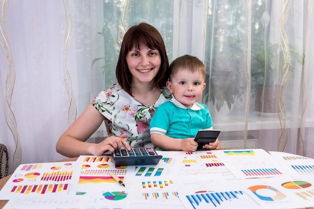 Analista de negocios de mujer con su hijo en la oficina