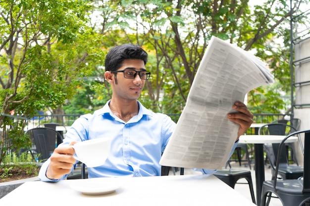Analista de negocios positivo tomando café y leyendo noticias.