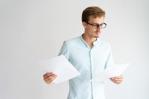 Analista sofisticado concentrado en papeles para ver gafas.