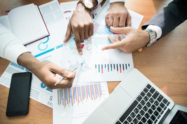 Analistas de negocios discutiendo gráficos en el lugar de trabajo