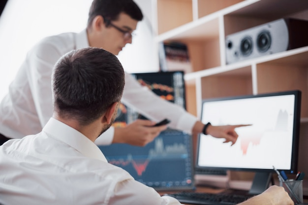 Analizando datos. primer plano del equipo de negocios jóvenes que trabajan juntos en la oficina creativa, mientras que la joven apuntando a los datos presentados en el gráfico con lápiz