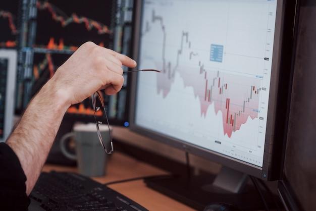 Analizando datos. primer plano del joven empresario señalando los datos presentados en el gráfico con la pluma mientras trabajaba en la oficina creativa