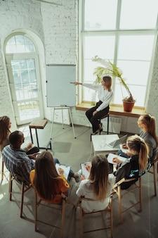 Analizando. oradora femenina dando presentación en el salón del taller. centro de negocios. vista trasera de los participantes en audiencia. evento de conferencia, formación. educación, diversidad, concepto inclusivo.