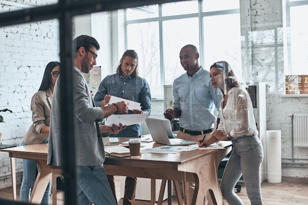 Analizando ventas. grupo de jóvenes modernos que se comunican juntos mientras trabajan detrás de la pared de vidrio en la sala de juntas