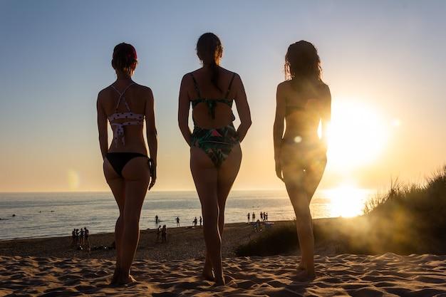Anapa, rusia - 03 de julio de 2020: tres mujeres jóvenes sexys en trajes de baño en el contexto de una puesta de sol de verano en una playa de arena se paran y miran el mar, vista trasera