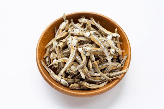 Anchoa seca en un tazón de madera sobre fondo blanco.