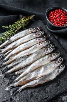 Anchoas crudas de pescado pequeño con pimiento y tomillo. fondo negro. vista superior.
