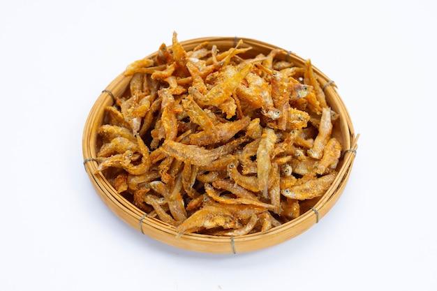 Anchoas fritas en canasta de bambú sobre fondo blanco.