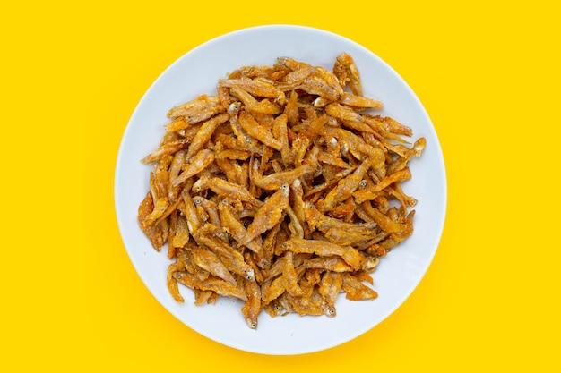 Anchoas fritas en plato blanco sobre fondo amarillo