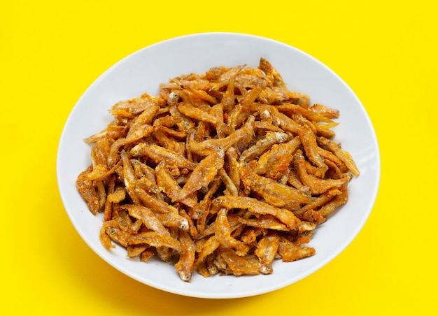 Anchoas fritas en plato blanco sobre fondo amarillo.