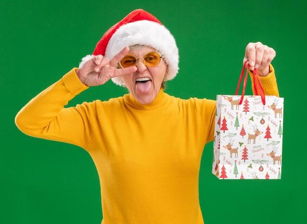 Anciana alegre en gafas de sol con sombrero de santa saca la lengua y sostiene una bolsa de regalo de papel gesticulando el signo de la victoria aislado en la pared verde con espacio de copia