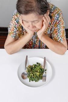 Anciana asiática aburrida con la comida